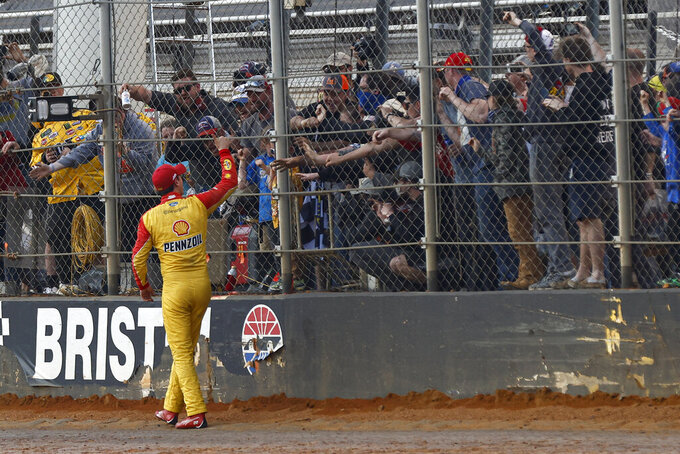 Joey Logano celebrates with fans after winning a NASCAR Cup Series auto race, Monday, March 29, 2021, in Bristol, Tenn. (AP Photo/Wade Payne)