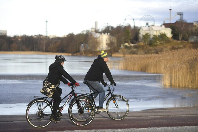 "In this photo taken on Wednesday, Jan. 1, 2020, cyclists enjoy a sunny day in Helsinki. Unusually mild weather in Finland left the southern part of the Nordic nation with a surprising absence of snow and an unusual delay in the start of ""thermal winter,"" meteorologists said. Mainland Finland recorded a high temperature of 7.9 degrees Celsius (46.2 F) and it reached 8.7 degrees Celsius (47.7 F) in the Aland Islands, an autonomous Baltic Sea region of Finland. (Vesa Moilanen/Lehtikuva via AP)"