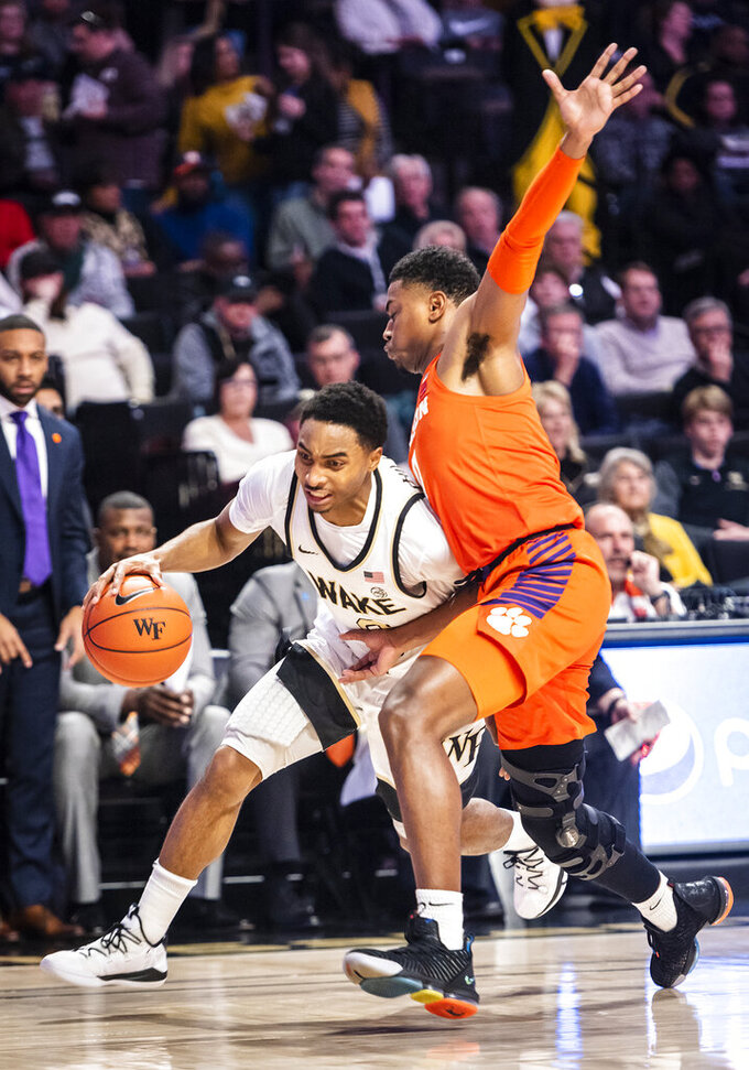 Wake Forest guard Brandon Childress (0) drives as Clemson guard Clyde Trapp defends during an NCAA college basketball game Saturday, Feb. 1, 2020, in Winston-Salem, N.C. (Andrew Dye/The Winston-Salem Journal via AP)