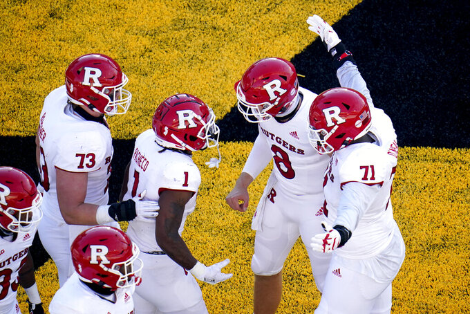 Rutgers running back Isaih Pacheco (1) and Artur Sitkowski (8) react with teammates Brendan Bordner (73) and Raiqwon O'Neal (71) after they connected for a touchdown pass during the second half of an NCAA college football game against Maryland, Saturday, Dec. 12, 2020, in College Park, Md. Rutgers won 27-24 in overtime. (AP Photo/Julio Cortez)