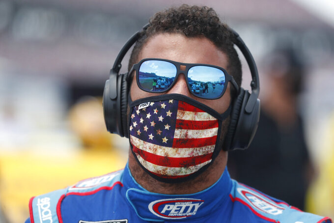 Driver Bubba Wallace walks to his car in the pits of the Talladega Superspeedway prior to the start of the NASCAR Cup Series auto race at the Talladega Superspeedway in Talladega Ala., Monday June 22, 2020. In an extraordinary act of solidarity with NASCAR's only Black driver, dozens of drivers pushed the car belonging to Bubba Wallace to the front of the field before Monday's race as FBI agents nearby tried to find out who left a noose in his garage stall over the weekend. (AP Photo/John Bazemore)