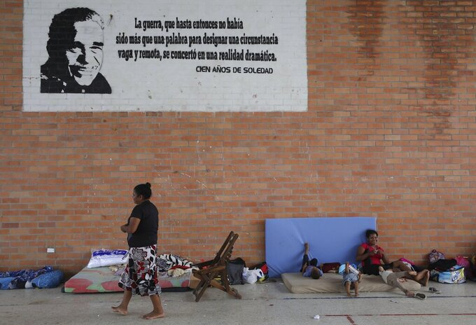 Venezuelans rest at a community center being used as a shelter in Arauquita, Colombia, Thursday, March 25, 2021, on the border with Venezuela. Thousands of Venezuelans are seeking shelter in Colombia this week following clashes between Venezuela's military and a Colombian armed group in a community along the nations' shared border. (AP Photo/Fernando Vergara)