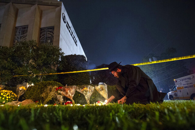 FILE - In this Oct. 27, 2018 photo, Rabbi Eli Wilansky lights a candle after a mass shooting at Tree of Life Synagogue in Pittsburgh's Squirrel Hill neighborhood. The three congregations sharing space at the Tree of Life synagogue relocated after an anti-Semitic gunman killed 11 worshippers. In March 2020, the congregations dispersed from their new locations due to the coronavirus pandemic and switched to virtual services. (Steph Chamber/Pittsburgh Post-Gazette via AP)