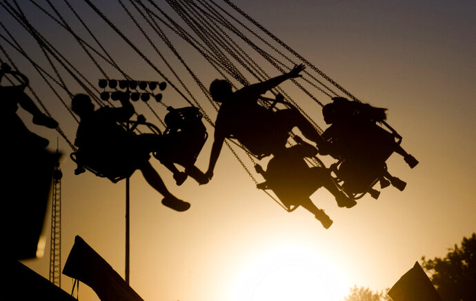 FILE - In this July 23, 2009 file photo, children are silhouetted by the setting sun as they ride a swing ride during the Canyon County Fair in Caldwell, Idaho. New results published Monday, Dec. 9, 2019,  in JAMA Pediatrics from the largest long-term study of brain development and children's health raise provocative questions about obesity and brain function.   (Greg Kreller/The Idaho Press-Tribune via AP, File)