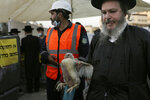 An ultra-Orthodox Jewish man carries a chicken to swing over his head as part of the Kaparot ritual in Jerusalem, Wednesday, Sept. 23, 2020. Observant Jews believe the ritual transfers one's sins from the past year into the chicken, and is performed before the Day of Atonement, Yom Kippur, the holiest day in the Jewish year, which takes place this year during a nationwide three-week lockdown to curb the spread of the coronavirus. A sanitation worker, center, stands ready to clean up the site, next to a yellow sign asking people to keep their distance. (AP Photo/Maya Alleruzzo)