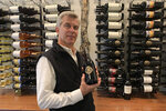 In this Oct. 4, 2019 photo, Michael Parr, vice president of international sales at Wente Vineyards, holds bottle of wine in a tasting room in Livermore, Calif. Caught in the crossfire of President Donald Trump's trade war with China, U.S. vineyards are struggling to sell Syrah in Shanghai and Chardonnay in Shenzhen. They risk losing their foothold in one of the world's fastest-growing wine markets.  Among the casualties is California's Wente Vineyards, a family-run wine business that was among the first U.S. winemakers to export to China 25 years ago. (AP Photo/Terry Chea)