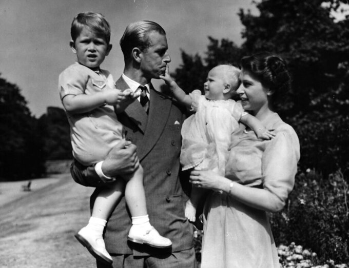 FILE - In this Aug. 1951 file photo, Princess Elizabeth stands with her husband the Duke of Edinburgh and their children Prince Charles and Princess Anne at the couple's London residence at Clarence House.  Buckingham Palace says Prince Philip, husband of Queen Elizabeth II, has died aged 99. (AP Photo/Eddie Worth, file)