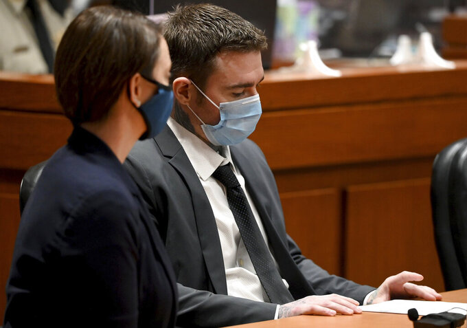 Kylr Yust, right, and attorney Molly Hastings sits at the defense table after the judge informed Yust of the jury's sentencing recommendations Friday, April 16, 2021, at the Cass County Justice Center in Harrisonville, Missouri. The jury in the murder trial recommended a sentence of 15 years for voluntary manslaughter of Kara Kopetsky and a life sentence (30 years) for the second-degree murder of Jessica Runions Friday, April 16, 2021. Sentencing is set for June 7. (Jill Toyoshiba/The Kansas City Star via AP)
