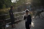 A girl waits for her friends as they walk to school in Kabul, Afghanistan, Sunday, Sept. 12, 2021. (AP Photo/Felipe Dana)
