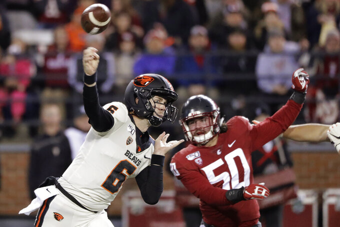 Oregon State quarterback Jake Luton (6) passes under pressure from Washington State defensive lineman Karson Block (50) during the first half of an NCAA college football game Saturday, Nov. 23, 2019, in Pullman, Wash. (AP Photo/Ted S. Warren)