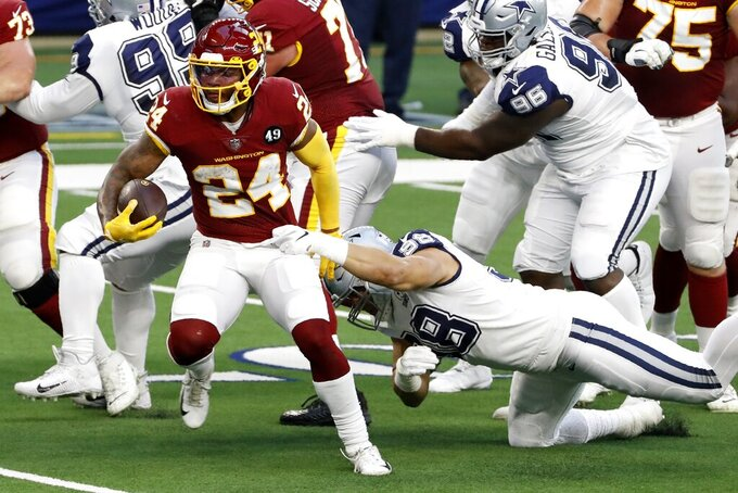 Washington Football Team running back Antonio Gibson (24) attempts to escape the grasp of Dallas Cowboys defensive end Tyrone Crawford (98) as he carries the ball in the first half of an NFL football game in Arlington, Texas, Thursday, Nov. 26, 2020. (AP Photo/Roger Steinman)