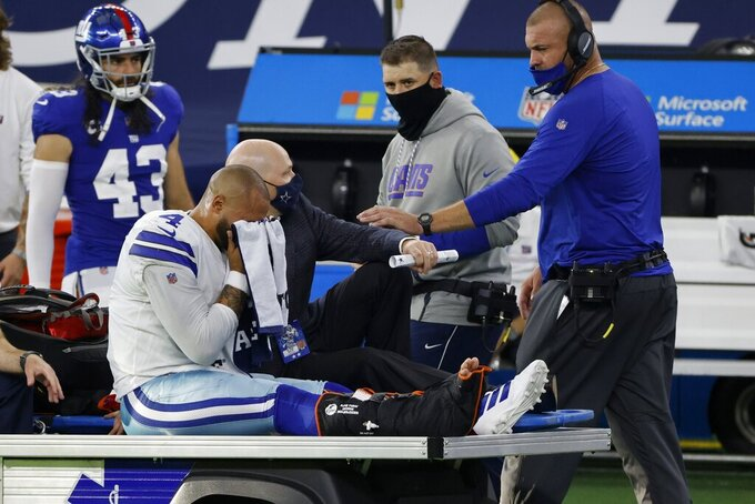 An emotional Dallas Cowboys quarterback Dak Prescott, wipes his face with a towel as he is carted off the field after suffering an unknown right lower leg injury in the second half of an NFL football game against the New York Giants in Arlington, Texas, Sunday, Oct. 11, 2020. The Giants' Nate Ebner (43) and staff look on. (AP Photo/Ron Jenkins)