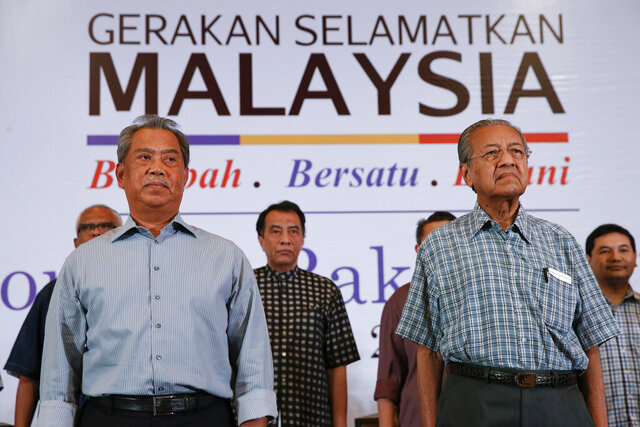 FILE - In this March 27, 2016, photo, Malaysia's former Prime Minister Mahathir Mohamad, right, and former Deputy Prime Minster Muhyiddin Yassin attend the