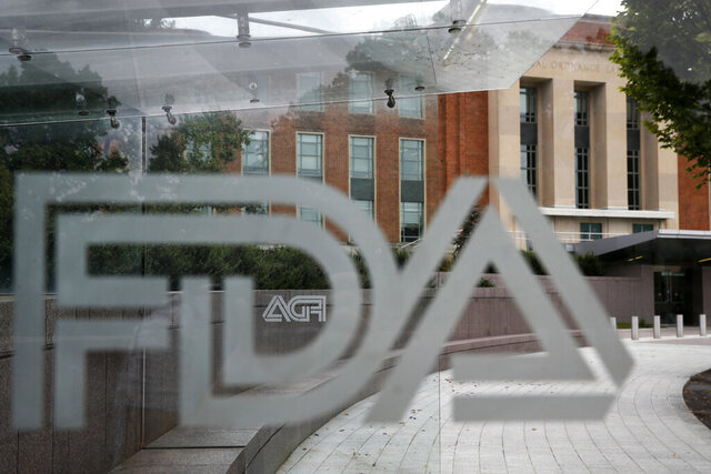 FILE - This Aug. 2, 2018, file photo shows the U.S. Food and Drug Administration building behind FDA logos at a bus stop on the agency's campus in Silver Spring, Md. Investors are driving shares of drug developer BioMarin down by a third after U.S. regulators rejected its potentially game-changing gene therapy for hemophilia A patients. The FDA's rejection late Tuesday, Aug. 18, 2020, means BioMarin will have to complete an ongoing late-stage patient study.  (AP Photo/Jacquelyn Martin, File)