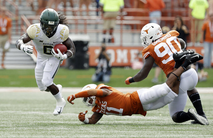 Baylor running back JaMycal Hasty (6) runs past the grasp of Texas defensive back P.J. Locke III (11) during the first half of an NCAA college football game, Saturday, Oct. 13, 2018, in Austin, Texas. (AP Photo/Eric Gay)