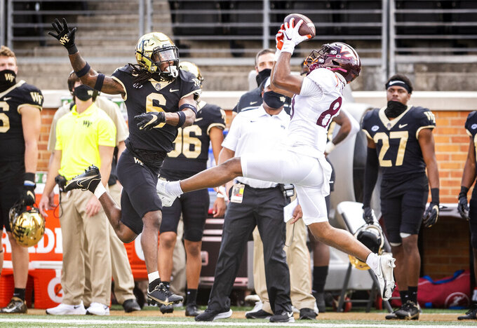 Virginia Tech wide receiver Tayvion Robinson (83) catches a pass over defense from Wake Forest defensive back Ja'Sir Taylor (6) during an NCAA college football game on Saturday, Oct. 24, 2020 at Truist Field in Winston-Salem, N.C. (Andrew Dye/The Winston-Salem Journal via AP)