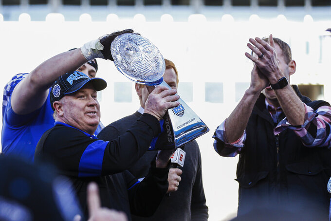 FILE - Kentucky head coach Mark Stoops, left, lifts the Belk Bowl trophy after his team defeated Virginia Tech 37-30 in the Belk Bowl NCAA college football game in Charlotte, N.C., Tuesday, Dec. 31, 2019. The winning culture Mark Stoops vowed to establish helped Kentucky avoid a huge falloff from its best season in a generation. (AP Photo/Nell Redmond, File)
