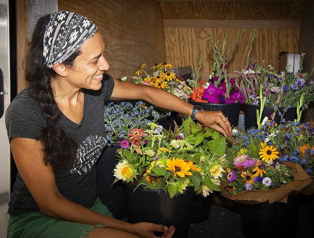 """Natasha Bowens Blair sorts buckets of fresh cut flowers in her trailer, July 19, 2020, Frederick, Md. """"Pretty much as soon as I stuck my hands into the dirt, and decided I was in love with growing and learning more about plants and the land, there was no way that I could do that without seeing the kind of intersection of race and injustice in our country,"""" she said. Bowens Blair is co-owner of Native Mountain Farm, which they describe as a """"women-owned, Black empowered"""" business located in Boonsboro, that serves customers in Frederick County. (Bill Green/The Frederick News-Post via AP)"""