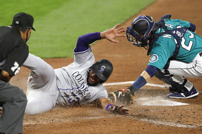 Colorado Rockies' Elias Diaz slides safely across home as Seattle Mariners catcher Austin Nola puts on a late tag in the third inning of a baseball game Friday, Aug. 7, 2020, in Seattle. (AP Photo/Elaine Thompson)