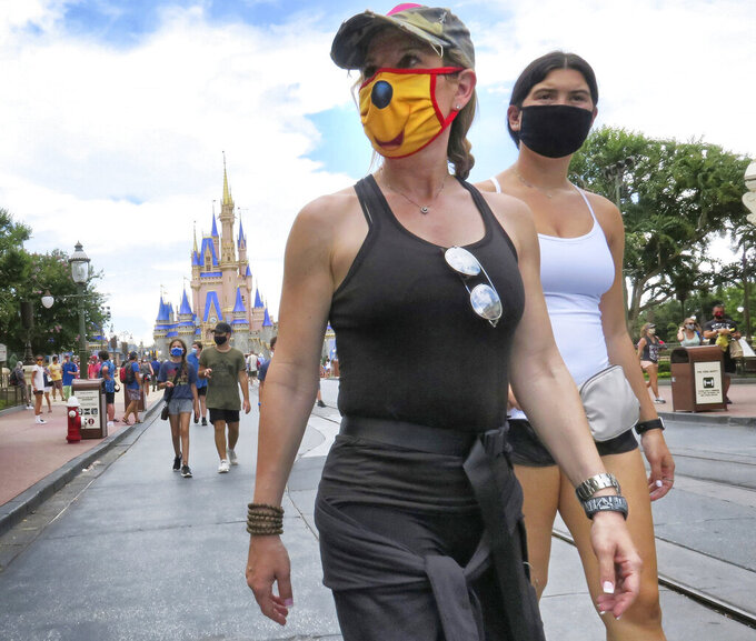 Guests wear masks as required to attend the official reopening day of the Magic Kingdom at Walt Disney World in Lake Buena Vista, Fla., Saturday, July 11, 2020. Disney reopened two Florida parks, the Magic Kingdom and Animal Kingdom, Saturday with limited capacity and safety protocols in place in response to the coronavirus pandemic. (Joe Burbank/Orlando Sentinel via AP)