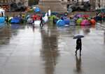 Protestors of the environmental activist group extinction rebellion camp during a demonstration during a rainy morning at Trafalgar Square in London, Monday, Oct. 14, 2019.(AP Photo/Frank Augstein)