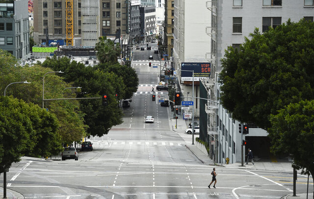 A jogger crosses a deserted 4th Street as stay-at-home orders continue in California due to the coronavirus, Friday, April 10, 2020, in downtown Los Angeles. (AP Photo/Chris Pizzello)