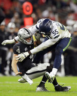 FILE - In this Oct. 14, 2018, file photo, Oakland Raiders quarterback Derek Carr (4) is sacked by Seattle Seahawks defensive end Frank Clark (55) during the second half of an NFL football game at Wembley stadium in London. The Seahawks placed a franchise tag on Clark before the NFL deadline on Tuesday, March 5, 2019. (AP Photo/Matt Dunham, File)