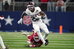 Texas A&M running back Isaiah Spiller (28) escapes a tackle attempt by Arkansas linebacker Grant Morgan, rear, in the first half of an NCAA college football game in Arlington, Texas, Saturday, Sept. 25, 2021. (AP Photo/Tony Gutierrez)