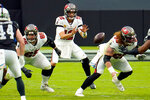 """FILE - In this Oct. 25, 2020, file photo, Tampa Bay Buccaneers quarterback Tom Brady (12) receives the ball from center Ryan Jensen (66) during the first half of the team's NFL football game against the Las Vegas Raiders in Las Vegas. """"It didn't take too long, really,"""" Jensen said of building a rapport with Brady. """"We both kind of have a fiery spirit and, you know, I think that has helped us quite a bit, getting to know each other and knowing what we're about.""""  (AP Photo/Jeff Bottari, File)"""