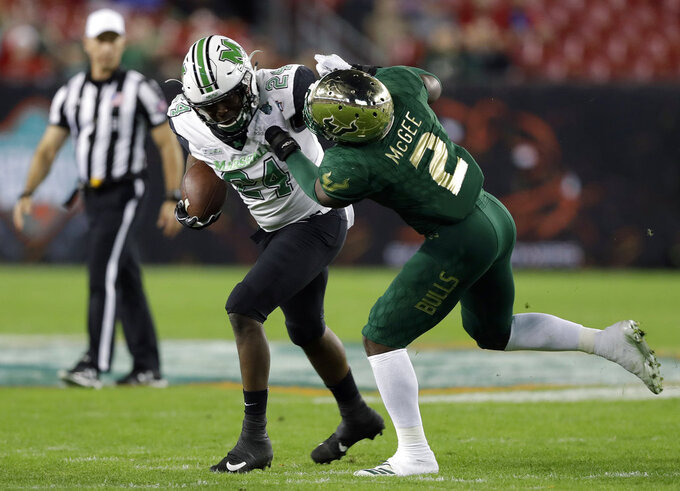 Marshall running back Keion Davis (24) is stopped by South Florida linebacker Khalid McGee (2) on a run during the first half of the Gasparilla Bowl NCAA college football game Thursday, Dec. 20, 2018, in Tampa, Fla. (AP Photo/Chris O'Meara)