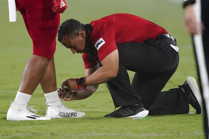 Southern Utah head coach Demario Warren ties the shoe of one of his players during the first half of an NCAA college football game against the Arizona State, Thursday, Sept. 2, 2021, in Tempe, Ariz. (AP Photo/Matt York)