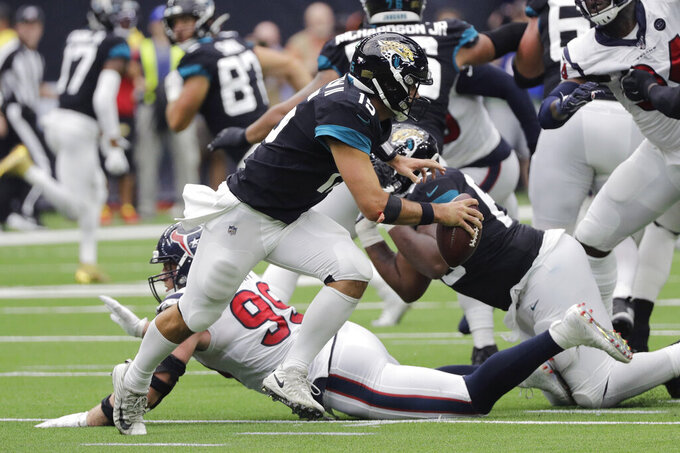 Jacksonville Jaguars quarterback Gardner Minshew (15) scramble past Houston Texans defensive end J.J. Watt (99) during the second half of an NFL football game Sunday, Sept. 15, 2019, in Houston. (AP Photo/David J. Phillip)