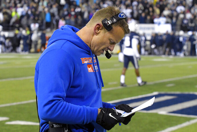 Boise State coach Bryan Harsin looks at a play sheet during the first half of the team's NCAA college football game against Utah State on Saturday, Nov. 23, 2019, in Logan, Utah. (AP Photo/Eli Lucero)
