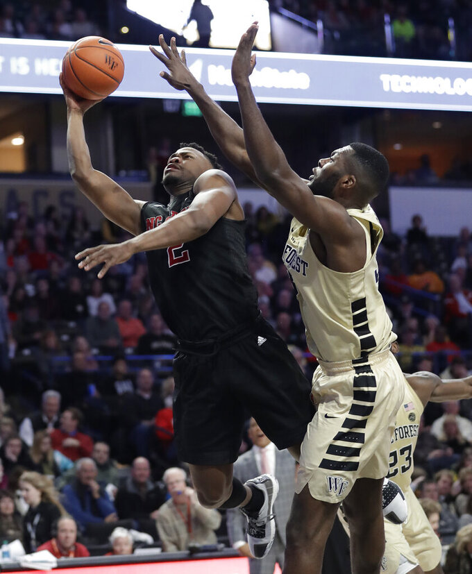 North Carolina State's Torin Dorn (2) drives past Wake Forest's Ikenna Smart during the second half of an NCAA college basketball game in Winston-Salem, N.C., Tuesday, Jan. 15, 2019. (AP Photo/Chuck Burton)