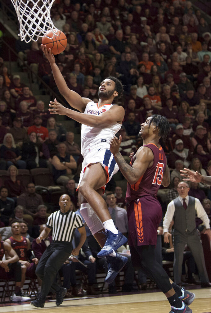 Virginia guard Braxton Key, left, drives past Virginia Tech defender Ahmed Hill, right, during the first half of an NCAA college basketball game in Blacksburg, Va., Monday, Feb. 18, 2019.(AP Photo/Lee Luther Jr.)