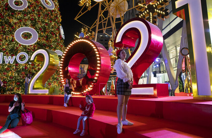 People pose for pictures with decorations made for New Year countdown celebrations outside a shopping mall in Bangkok, Thailand, Tuesday, Dec. 29, 2020. Thailand ordered to scaled down gathering for New Year celebrations after reporting more than 155 new coronavirus infections and its first fatality since November on Tuesday. (AP Photo/Gemunu Amarasinghe)