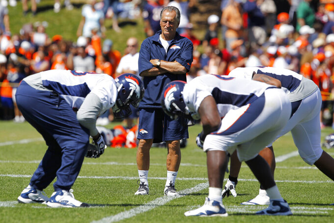FILE - Denver Broncos offensive line consultant Alex Gibbs, back, looks on as linemen take part in drills after the morning session at the team's NFL training camp in Englewood, Colo., in this Tuesday, Aug. 6, 2013, file photo. Gibbs, the innovative offensive line coach whose zone-blocking scheme helped lead the Denver Broncos to back-to-back Super Bowl triumphs in the 1990s, has died at age 80, the team said. The team said Gibbs died Monday, July 12, 2021,  from complications of a stroke with family by his side in his Phoenix home. (AP Photo/David Zalubowski, File)