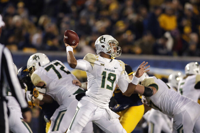 Baylor quarterback Jalan McClendon (19) attempts a pass during the second half of an NCAA college football game against Wet Virginia, Thursday, Oct. 25, 2018, in Morgantown, W.Va. (AP Photo/Raymond Thompson)