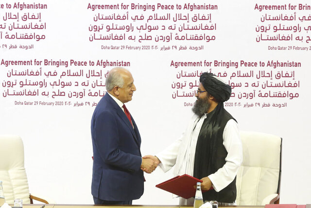 U.S. peace envoy Zalmay Khalilzad, left, and Mullah Abdul Ghani Baradar, the Taliban group's top political leader shack hands after signing a peace agreement between Taliban and U.S. officials in Doha, Qatar, Saturday, Feb. 29, 2020. The United States is poised to sign a peace agreement with Taliban militants on Saturday aimed at bringing an end to 18 years of bloodshed in Afghanistan and allowing U.S. troops to return home from America's longest war. (AP Photo/Hussein Sayed)