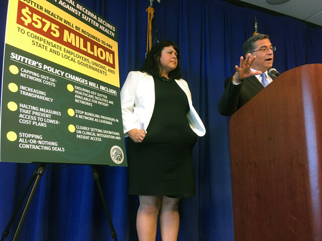 California Attorney General Xavier Becerra, right, is joined by senior adviser Melanie Fontes-Rainer, left, during a news conference in Sacramento, Calif. on Friday, Dec. 20, 2019. One of Northern California's largest health systems is paying $575 million to settle claims that it used anti-competitive practices to bump up costs for patients. Becerra on Friday called the settlement with Sutter Health one of the nation's largest actions against anti-competitive conduct in the health care marketplace. (AP Photo/Don Thompson)