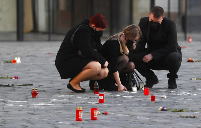 People pay respect to victims of the COVID-19 pandemic at a spontaneous memorial place set at the Old Town Square in Prague, Czech Republic, Monday, March 29, 2021. The coronavirus pandemic is unleashing enormous suffering as infection rates rise across central Europe even as the Czech Republic and Slovakia, recently among the worst-hit areas in the world, are finally seeing some improvements following tight lockdowns. (AP Photo/Petr David Josek)
