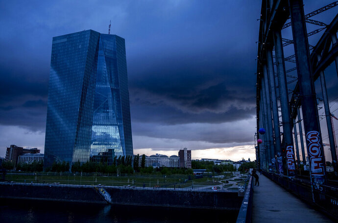 FILE - In this file photo dated Friday, May 1, 2020,  the European Central Bank is shadowed by heavy clouds in Frankfurt, Germany.  The central bank for the 19 countries that use the euro said Thursday June 18, 2020, That it has handed out more than a trillion euros in cheap loans to banks as part of its effort to get the economy through the virus outbreak.  (AP Photo/Michael Probst, FILE)