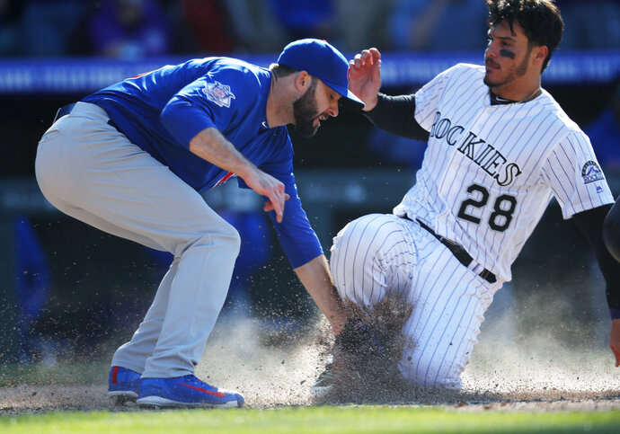 Chicago Cubs relief pitcher Brandon Morrow, left, tags out Colorado Rockies' Nolan Arenado at home plate as he tries to advance to score but instead becomes the final out in the bottom of the ninth inning of a baseball game Sunday, April 22, 2018, in Denver. The Cubs won 9-7. (AP Photo/David Zalubowski)