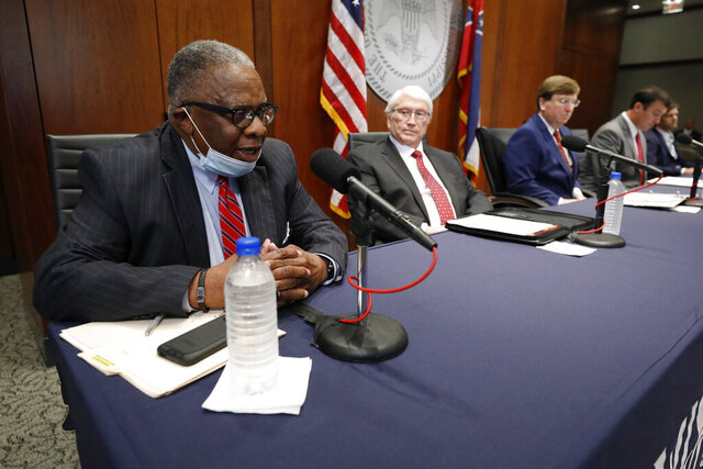 Vicksburg, Miss., Mayor George Flaggs, left, speaks about the search committee's suggestion that Burl Cain, the former warden of the Louisiana State Penitentiary, commonly known as Angola, seated second from left, be selected by Gov. Tate Reeves, second from right, as the new commissioner of the Mississippi Department of Correction, during Reeves' daily coronavirus update for media, Wednesday, May 20, 2020 in Jackson, Miss. (AP Photo/Rogelio V. Solis)