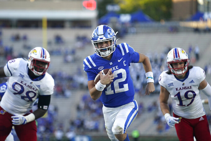 Duke quarterback Gunnar Holmberg (12) runs for a touchdown while Kansas defensive lineman Caleb Sampson (98) and linebacker Gavin Potter (19) give chase during the second half of an NCAA college football game in Durham, N.C., Saturday, Sept. 25, 2021. (AP Photo/Gerry Broome)