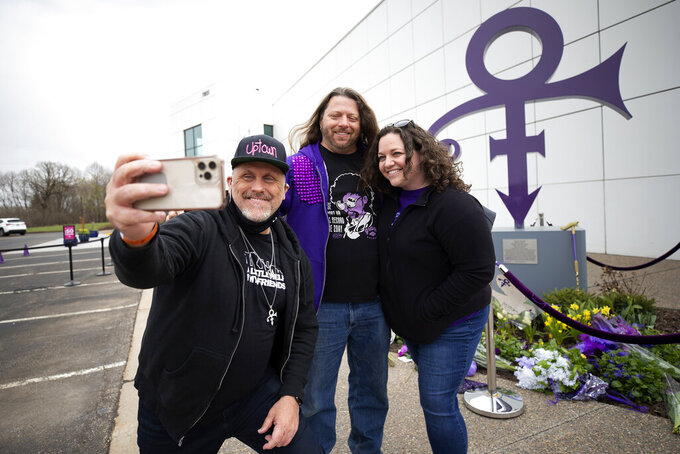 Prince fans were invited to Paisley Park, 20 at a time, to pay respect to the legendary musician and artist during the 5th anniversary of his death, Wednesday, April 21, 2021, in Chanhassen Minn. Fans took photos in front of the iconic Prince symbol statue outside of the museum before entering. (AP Photo/Stacy Bengs)