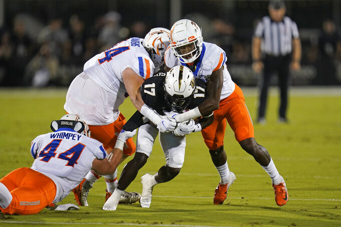 Central Florida wide receiver Amari Johnson (17) is stopped by Boise State linebacker Riley Whimpey (44), defensive tackle Jackson Cravens, center, and cornerback Tyric LeBeauf during the first half of an NCAA college football game Thursday, Sept. 2, 2021, in Orlando, Fla. (AP Photo/John Raoux)