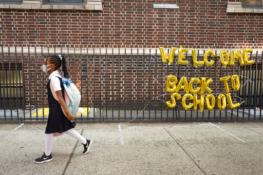 """FILE - In this Sept. 13, 2021, file photo, a girl passes a """"Welcome Back to School"""" sign as she arrives for the first day of class at Brooklyn's PS 245 elementary school in New York. COVID-19 deaths and cases in the U.S. have climbed back to where they were over the winter, fueled by children now back in their classrooms, loose mask restrictions and low vaccination levels. (AP Photo/Mark Lennihan, File)"""