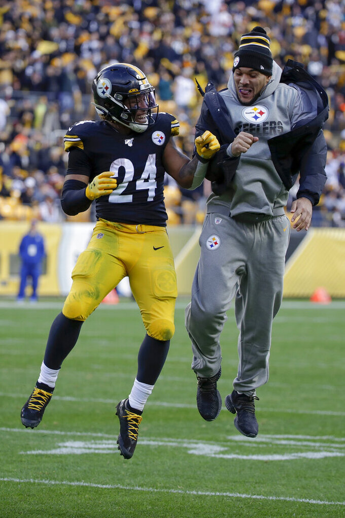 Pittsburgh Steelers running back Benny Snell (24) leaps in celebration with injured running back James Conner (30) after he scored against the Cleveland Browns during the second half of an NFL football game, Sunday, Dec. 1, 2019, in Pittsburgh. (AP Photo/Gene J. Puskar)