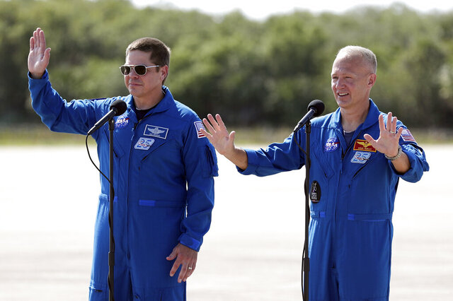 NASA astronauts Bob Behnken, left, and Doug Hurley wave as they leave a news conference after they arrived at the Kennedy Space Center in Cape Canaveral, Fla., Wednesday, May 20, 2020. The two astronauts will fly on the SpaceX Demo-2 mission to the International Space Station scheduled for launch on May 27. (AP Photo/John Raoux)